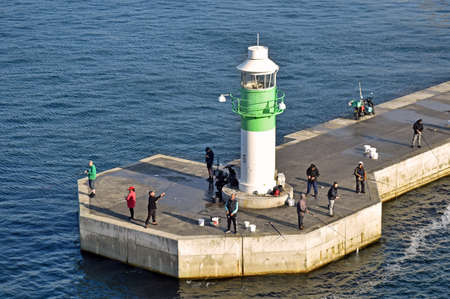 Aarhus, Denmark - July 20, 2017: Some people are fishing in the morning sun at the green-and-white striped lighthouse on the pier of Aarhus city in Denmark. 新聞圖片