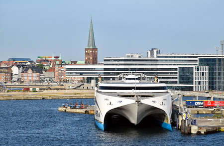 Aarhus, Denmark - July 20, 2017: The high-speed ferry EXPRESS 1 of the shipping company Molslinjen is moored at the pier in the port of Aarhus (Denmark). In the background are historical as well as modern buildings of the city center.