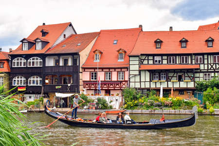 Bamberg, Germany - July 12, 2018: A gondolier with a Venetian gondola moving on the river Regnitz walking along historic half-timbered houses in the old town of Bamberg (Germany).