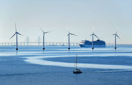Copenhagen, Denmark - July 15, 2017: A very large passenger ship and a small sailboat pass offshore wind turbines near the Oresund Bridge between Denmark and Sweden