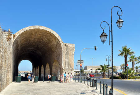Heraklion, Greece - July 15, 2016: Passersby cross the vaults of the former Venetian shipyards in Heraklion on the island of Crete.