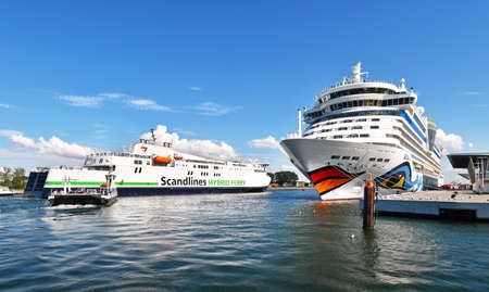 Warnemunde, Germany - July 14, 2017: Ship traffic on the sea in Warnem?nde - the cruise ship AIDAdiva has moored at the cruise terminal and the ferry. Copenhagen is arriving from Denmark; a small car ferry crossing the canal 新聞圖片