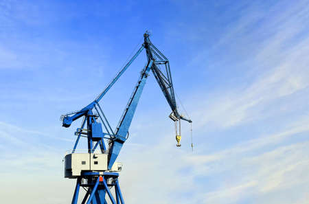 Port crane against a blue sky with a light cloud cover Stock Photo