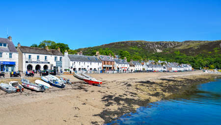 Ullapool, United Kingdom - June 24, 2018: Coast with small houses in the Ullapool village in Scotland. In the background the highlands can be seen