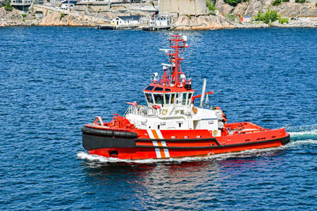 Red tugboat goes for a mission from the harbor out to sea Stock Photo - 107139725