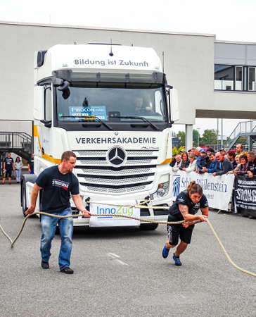 Chemnitz, Germany - October 4, 2015: A heavy woman pulls on a heavy vehicle during a weight training and commercial vehicle presentation in Chemnitz, Germany. A man assisting the athlete, by holding the rope.