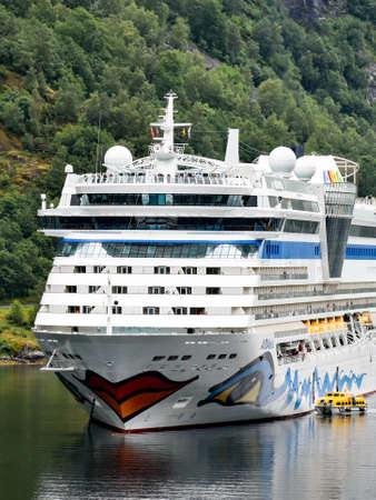 Geiranger, Norway - July 17, 2017: AIDAbella's shipping company AIDA Cruises has anchored in the Geiranger fjord. Passengers are transported on land for a shore excursion with tender boats. 新聞圖片
