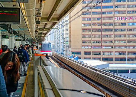 Kwun Tong, Hong Kong - February 9, 2016: Passengers are waiting on the Green Line MTR train train at Kwun Tong Station. 新聞圖片