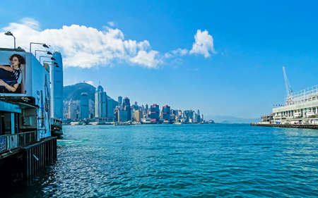 Tsim Sha Tsui, Hong Kong - February 9, 2016: View over Victoria Harbor to the skyline of Hong Kong Island with its skyscrapers.