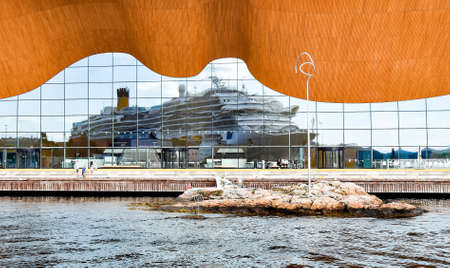 Kristiansand, Norway - July 19, 2017: The cruise ship Costa Favolosa of Costa Cruises is reflected in the glass facade of the Kilden Performing Arts Center