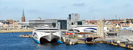 Aarhus, Denmark - July 20, 2017: The high-speed ferry EXPRESS 1 of the shipping company Molslinjen is moored in the port of Aarhus (Denmark). In the background are historical as well as modern buildings of the city center 版權商用圖片 - 135906368
