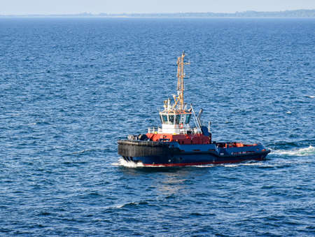 A tugboat navigates on the sea, in the background the coast can be seen