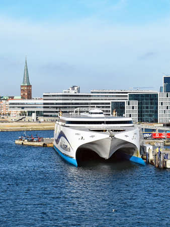 Aarhus, Denmark - July 20, 2017: The high-speed ferry EXPRESS 1 of the shipping company Molslinjen is moored in the port of Aarhus (Denmark). In the background are historical as well as modern buildings of the city center