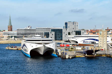 Aarhus, Denmark - July 20, 2017: The high-speed ferries EXPRESS 1 and EXPRESS 2 of the shipping company Molslinjen are moored in the port of Aarhus (Denmark). In the background are historical as well as modern buildings of the city center. 版權商用圖片 - 144086451