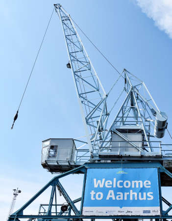 Aarhus, Denmark - July 20, 2017: Harbor crane in Aarhus on which an advertising poster is attached to welcome cruise guests. 新聞圖片