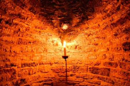 Burning candle in a dark cellar niche, which was built with bricks 版權商用圖片