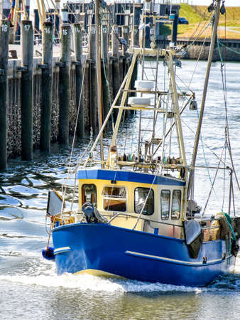 A small fishing boat enters the harbor of B?sum in North Frisia in Germany. 版權商用圖片