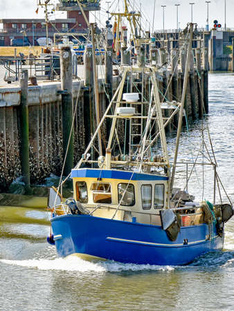 A small fishing boat enters the harbor of Busum in North Frisia in Germany. 版權商用圖片