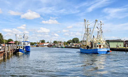 Buesum, Germany? August 1, 2018: A fishing boat enters the harbor of B?sum in North Frisia in Germany. 版權商用圖片 - 147834012