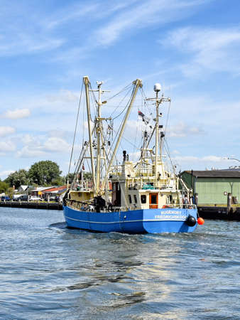 Buesum, Germany? August 1, 2018: A fishing boat enters the harbor of B?sum in North Frisia in Germany. 版權商用圖片 - 148278272