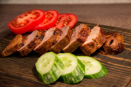 Sliced roasted meat with tomatoes and cucumber on a wooden board