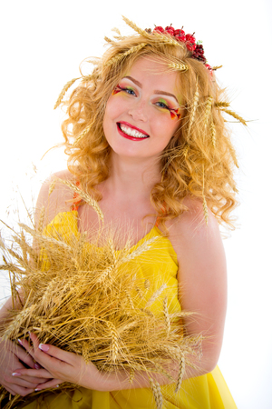 un healthy: Beautiful girl dressed yellow with wheaten ears. Red-haired girl with freckles in an image of hot summer.
