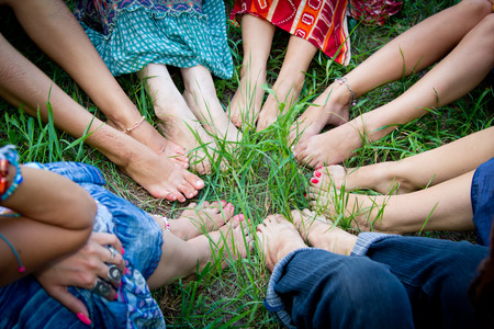 Bare feet of group of young girls in a circle on a green grass Stockfoto