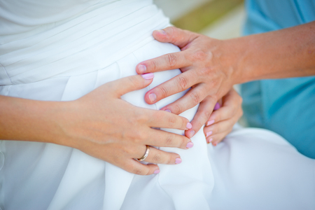 loving hands: The gentle loving hands of future father and future mother on a stomach of the pregnant woman. Stock Photo