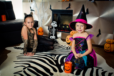 disguised: Two girls disguised as a tiger and as a witch are waiting for some candies in All Saints Day. Halloween at home.