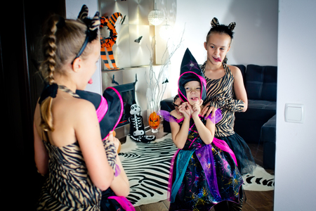 disguised: Two girls disguised as a tiger and as a witch are wriggling in front of the mirror in All Saints Day. Halloween at home.
