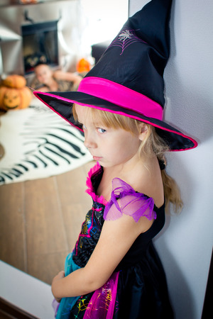 disguised: The little girl disguised as the witch is standing near a mirror and looking in the camera. There is a Halloween decor in the room  in All Saints Day. Halloween at home.