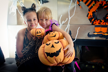 disguised: Two girls disguised as a tiger and as a witch are holding three festive pumpkins in their hands  in All Saints Day. Halloween at home.