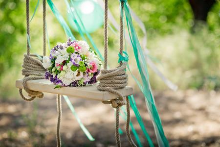 Wedding decor. A bridal bouquet on a decorative swing.Outdoor.