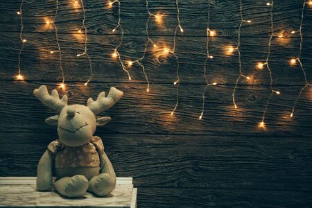 Garland Lights, toy deer on old grunge wooden board. Christmas and New Year decoration.  Christmas lighting on wooden planks