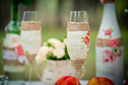 Wedding decor with wedding glasses in style of a shabby chic, bottles, peaches. Decoration of a wedding photoshoot.  Details of a wedding decor. Zdjęcie Seryjne