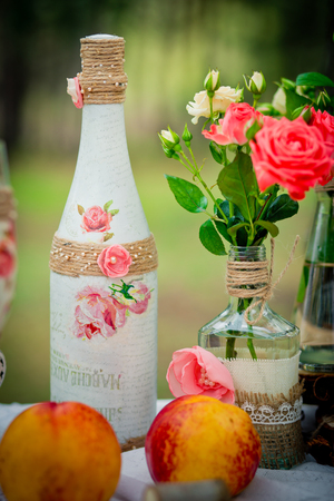 Wedding decor with wedding bottles in style of a shabby chic and peaches. Decoration of a wedding photoshoot.  Details of a wedding decor.