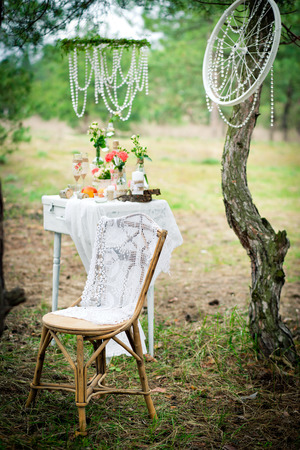Ancient chair against wedding decoration in style of a shabby chic. Decoration of a wedding photoshoot.  Details of a wedding decor. Zdjęcie Seryjne