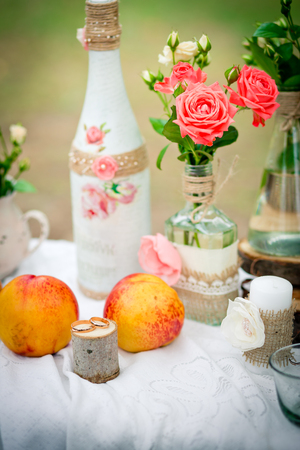 Wedding decor with wedding rings,  and peaches, bottles and candles  in style of a shabby chic. Decoration of a wedding photoshoot.  Details of a wedding decor. 版權商用圖片