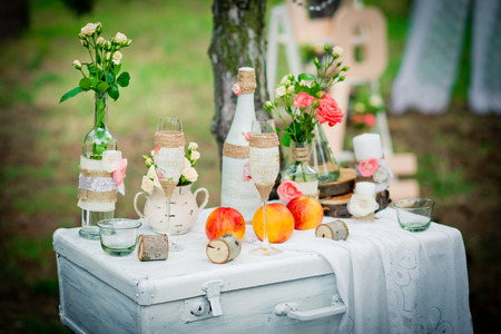 Wedding decor with bottles, glasses, roses, vases and peaches on a ancient suitcase. Decoration of a wedding photoshoot.  Details of a wedding decor. 版權商用圖片