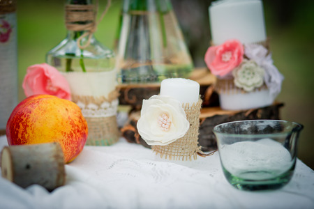 Wedding decor with wedding rings, peaches,  roses, candles and bottles  in style of a shabby chic. Decoration of a wedding photoshoot.  Details of a wedding decor.