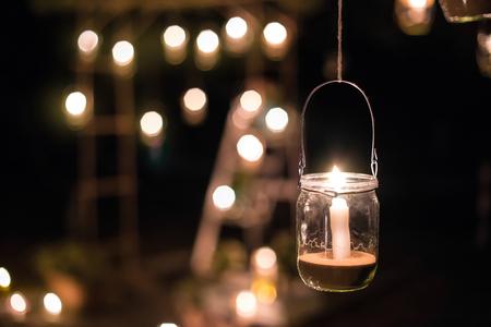 Lampa wykonana ze słoika ze świecą wisi na drzewie w nocy. Noc poślubna wystrój. ceremonia noc