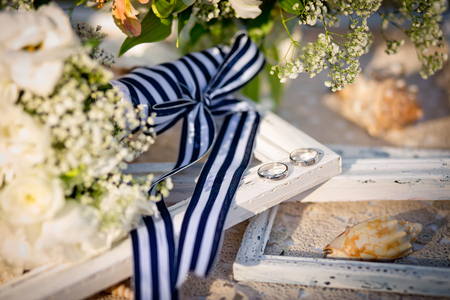 Wedding rings, bridal bouquet with striped sea ribbon, cockleshells, a framework for a photo. A wedding decor in sea style.