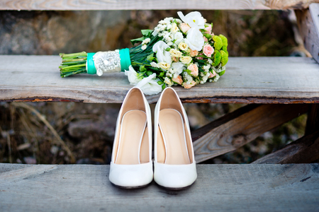 Womans wedding shoes on the wooden ladder with the bouquet of flowers next to them. The bouquet is tied by the white line decorated with pastes. Zdjęcie Seryjne