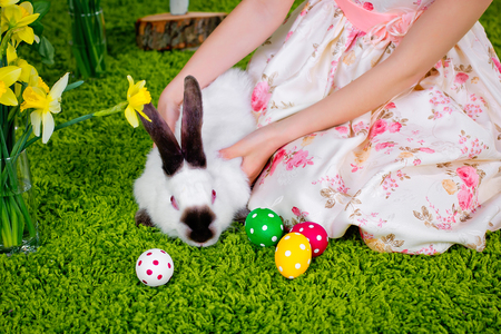 The girl is playing with an Easter rabbit and Easter eggs on a green carpet