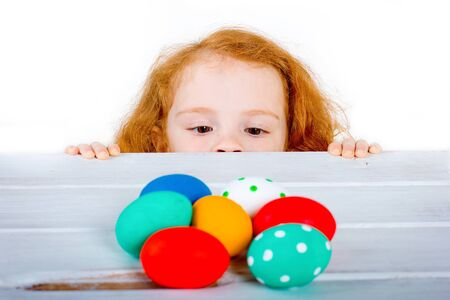 The little cute red-haired girl with freckles are looking at Easter eggs