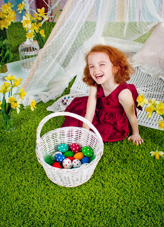 The red-haired girl is laughing near an easter basket. Basket with Easter eggs near the laughing girl. Top view