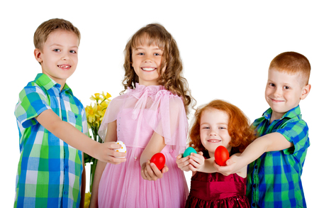 Two boys and two girls hold Easter eggs in straight arms. Four hildren are showing Easter eggs. White background.