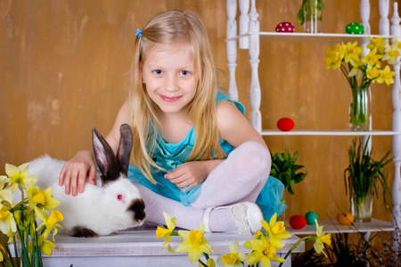 The lovely fair-haired girl is stroking an easter rabbit next to narcissus.