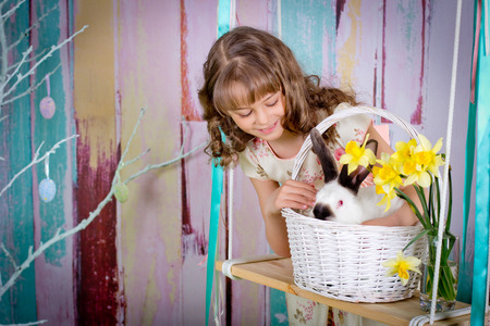 The girl are playing with Easter rabbit in a basket on a swing