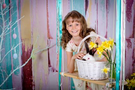 The smiling girl and easter rabbit in a basket on a swing.